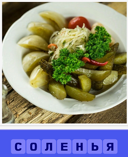 в тарелке лежат разные соленья, огурцы и капуста с морковкой