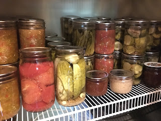 Photo of home canned food, including pickle relish, whole tomatoes, pickled green beans, salsa, jams, mustard, and pickles. https://trimazing.com/
