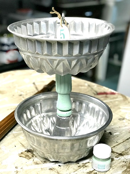 Stacked bundt pans with green chair leg post