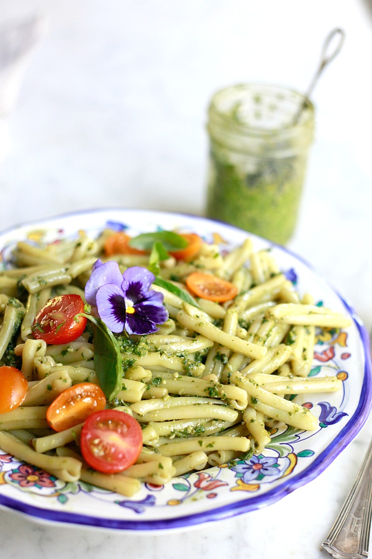 A bowl of homemade pesto pasta with tomatoes.