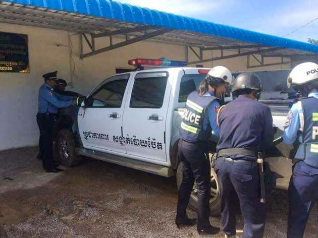 Police remove black vinyl covering form a car in Poipet after it was seized for have a siren and incorrect number plates. Photo supplied
