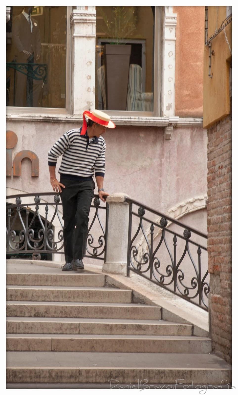 Gondolero con traje típico a rayas y sombrero en un puente de Venecia