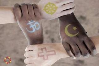 Foto vista de cima, ao centro, quatro mãos formam um vão quadrado no meio, em paralelo aos pares, duas brancas e duas negras, uma segura o punho da outra. No dorso de cada mão há uma tatuagem: brancas em paralelo horizontal: o símbolo do Budismo (uma mandala em verde limão) e do Cristianismo (a cruz delineado em vermelho); negras em paralelo vertical: a sílaba sagrada do Hinduísmo, Om, em azul claro, e do Islamismo(meia lua e uma estrela em amarelo).