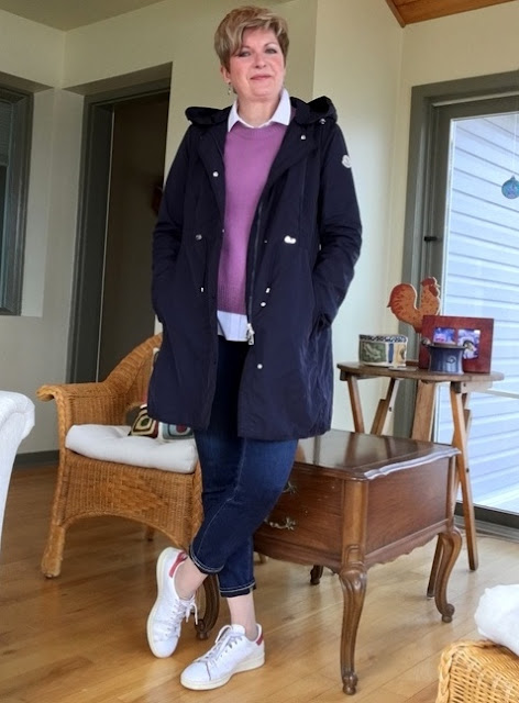 woman in jeans, sneakers, pink sweater, and blue anorak
