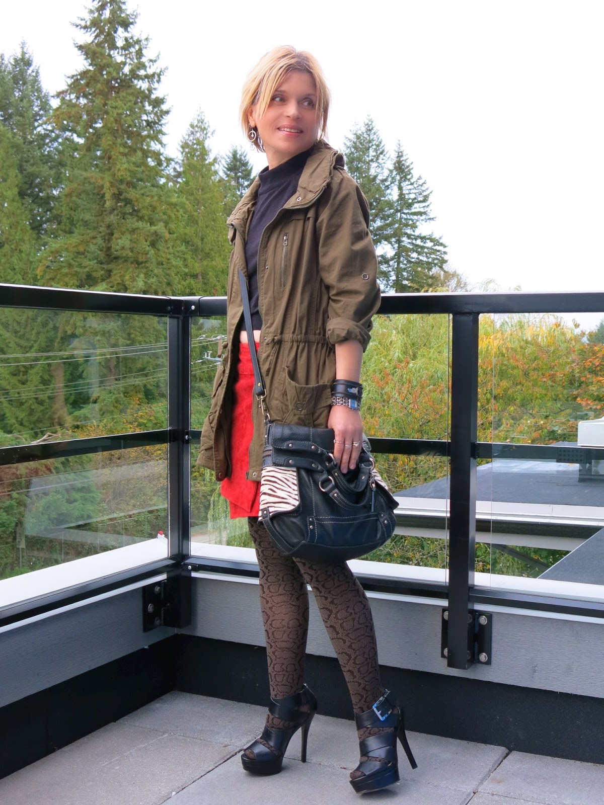 styling a red envelope skirt with a cropped sweater, patterned tights, military-inspired jacket, and Michael Michael Kors heels