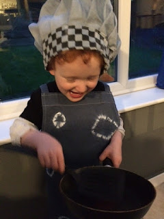 Very happy boy dressed as a chef holding a pan and spatula