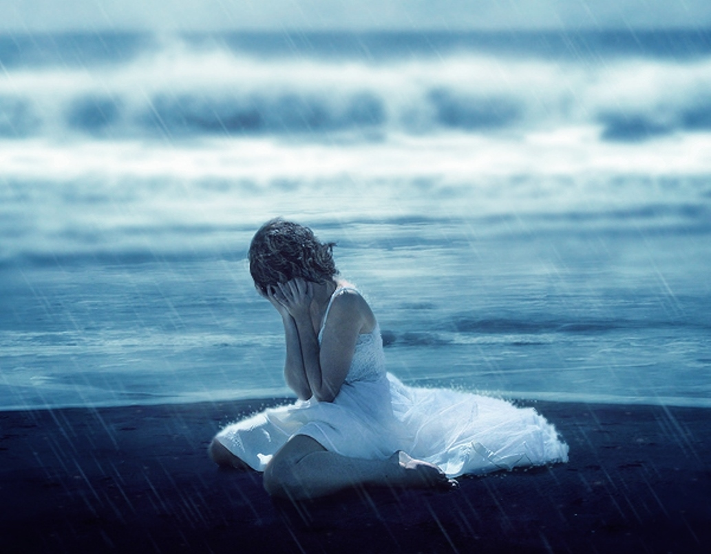 Lonely girl crying with tears in rain thinking of forgotten love and lost dreams