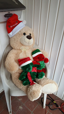 large bear in santa hat sitting in a chair with two small bears, red and green, in his lap