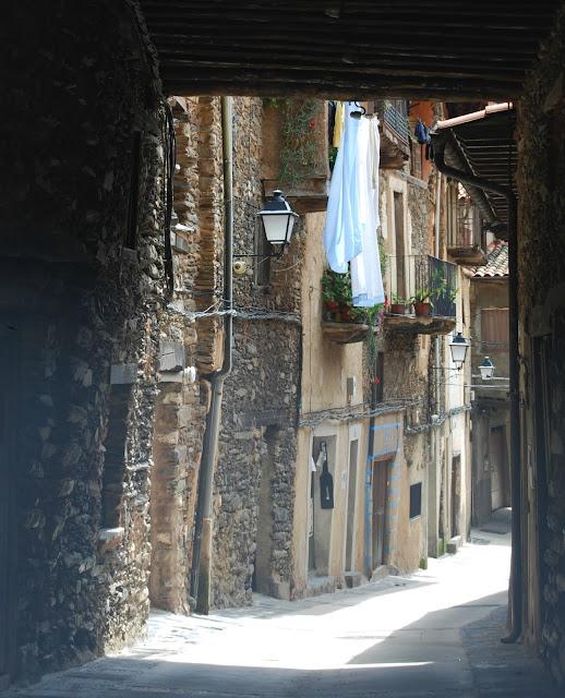 Vista de una calle de Robledillo de Gata con fachadas de piedra y madera y ropa tendida