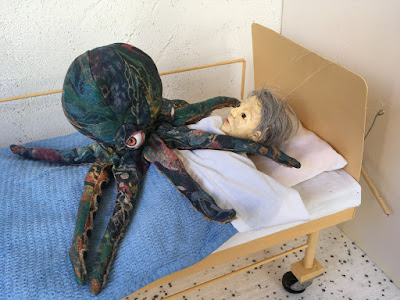 Octopus puppet on puppet in hospital bed, pinning her down, taking away her voice