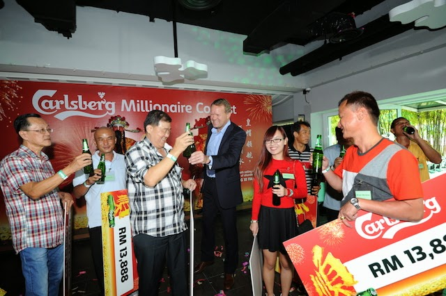hat calls for a Carlsberg: Henrik Juel Andersen, Managing Director of Carlsberg Malaysia [third from right] congratulates Lim Chong Boon [third from left] after having become the first ever Carlsberg Millionaire