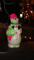 light up snowman wearing promotional St. Patty's Day Necklace