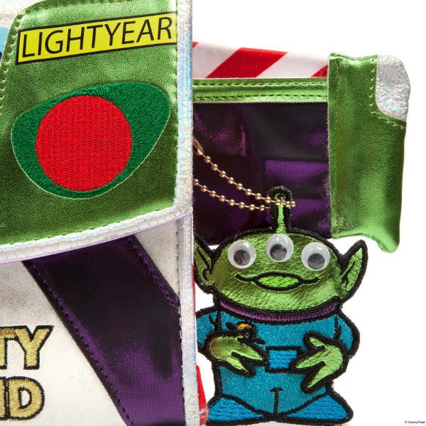 small metallic alien charm with googly eyes dangling from side of metallic handbag