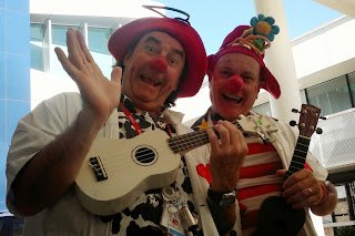 Two clown doctors wearing white coats, stethoscopes around their funny hats, red noses and carrying ukeleles.
