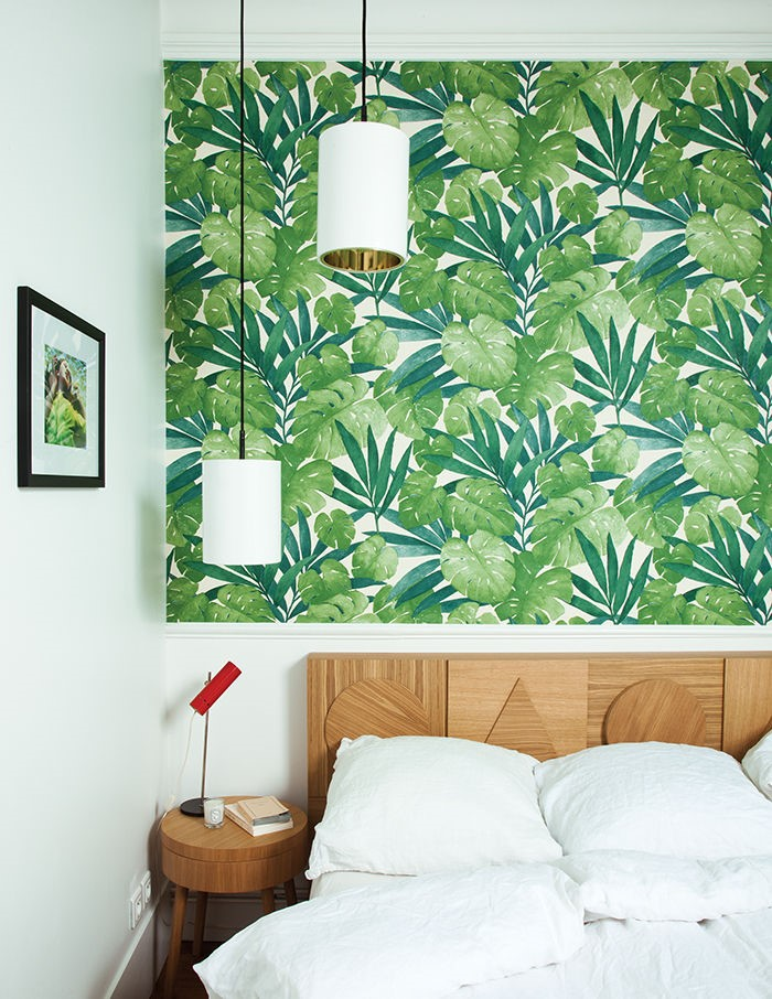 Banana leaf wallpaper detail over a wooden bed with white bedding
