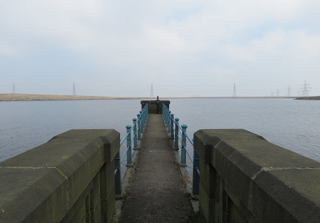 View directly down a stone jetty with blue iron railings that stretches out into the reservoir. Over the water, a line of pylons stretches across the moor.