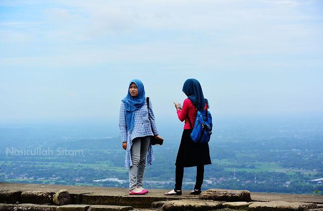 Dua gadis berjilbab menikmati pemandangan dari pelataran candi ijo