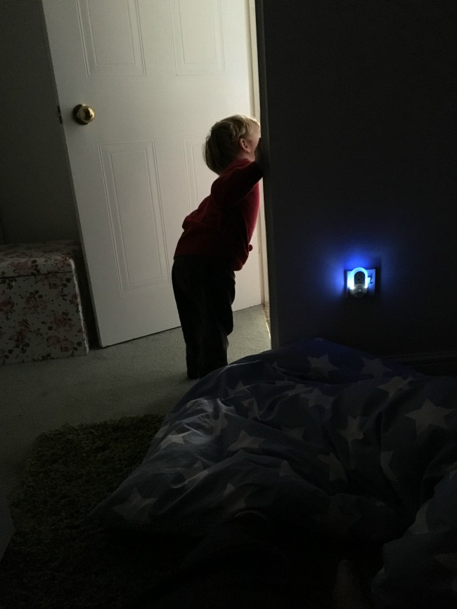 silhoutte-of-toddler-looking-out-of-dark-bedroom-into-lit-hallway
