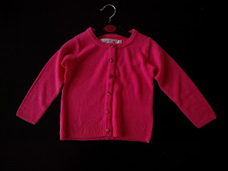 small red cardigan on a hanger