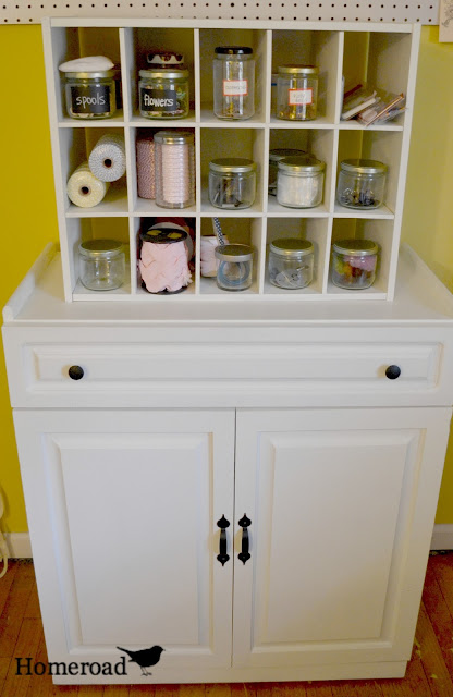 front view of white craft cabinet with jars in cubbies