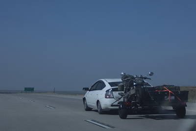 a photo of a Prius towing a trailer, carrying a groovy motorcycle.