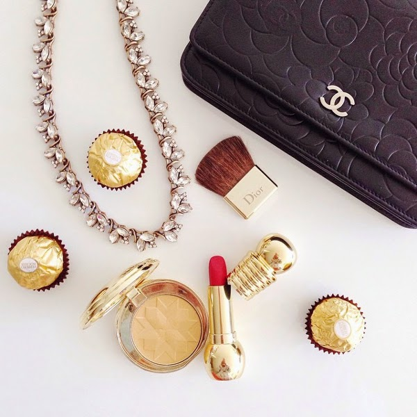 flat lay featuring rhinestone necklace, Chanel camellia-embossed wallet on chain WOC, Ferrero Rocher chocolates, Dior makeup