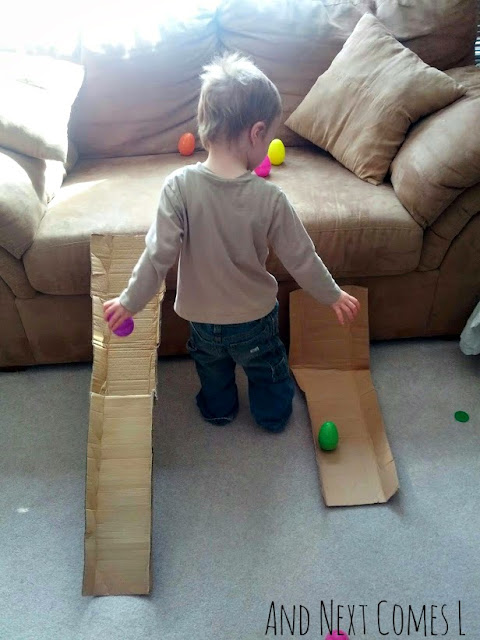 J trying to race wobbly Easter eggs on two cardboard ramps from And Next Comes L