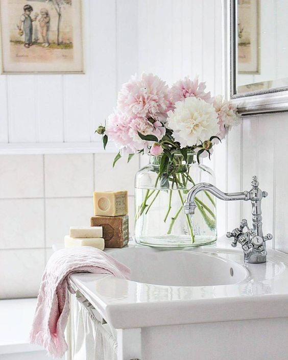 Gorgeous pink and white flowers on sink in farmhouse bathroom