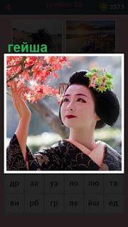 стоит гейша и руками трогает ветки дерева с цветами