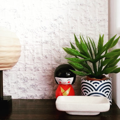 One-twelfth scale Japanese-themed display on a chest of drawers, with a rice-paper lamp. a kokeshi dolls, a plant in a blue-and-white Japanese pot and a white rectangular bowl.