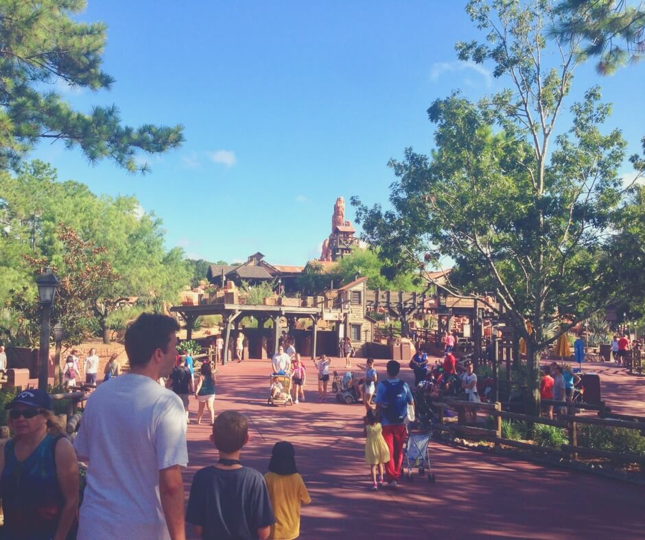 People head towards Big Thunder Mountain in Magic Kingdom, one of our favourite rides. The sun is shining and the skies are blue. Large trees surround the area shading the path leading to the ride.