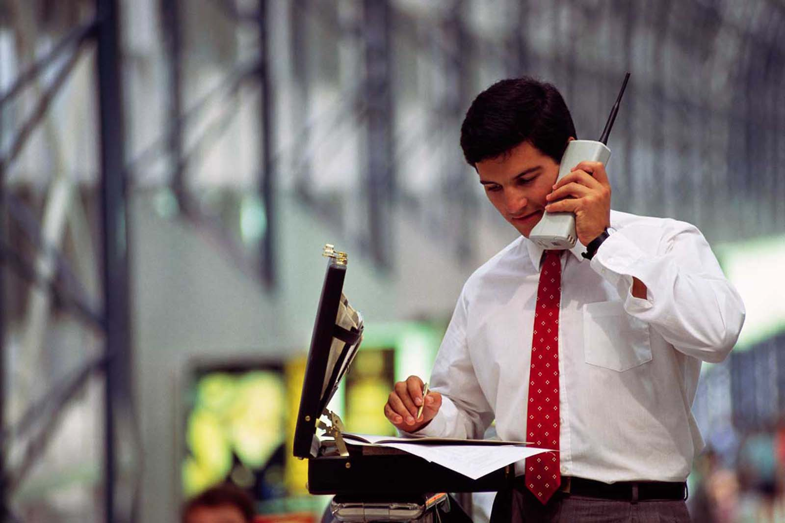 A young businessman with a brief case goes over figures on a giant old cell phone. 1990.