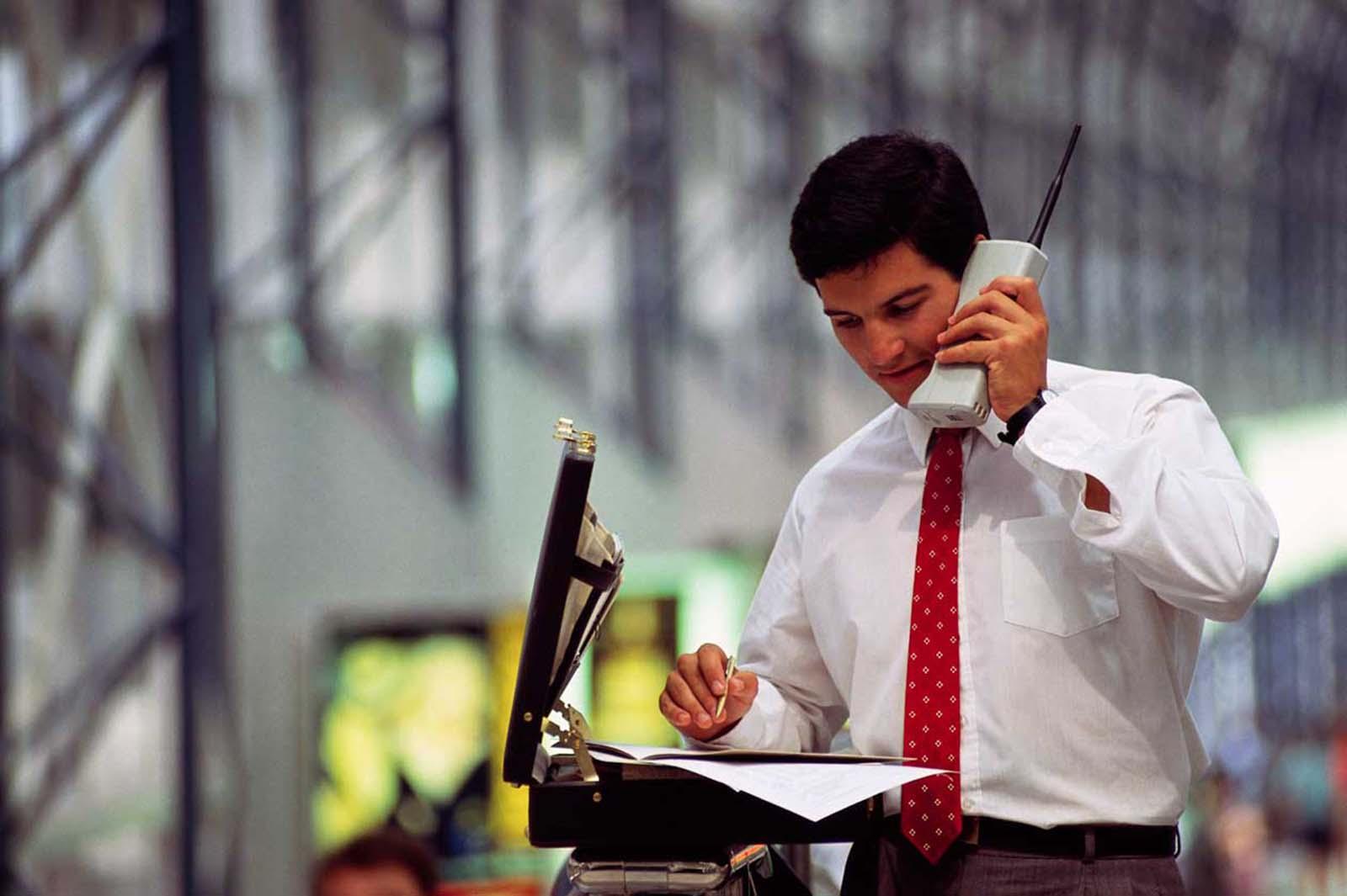 Um jovem empresário, com uma maleta, repassa números num gigantesco telefone celular antigo. 1990.