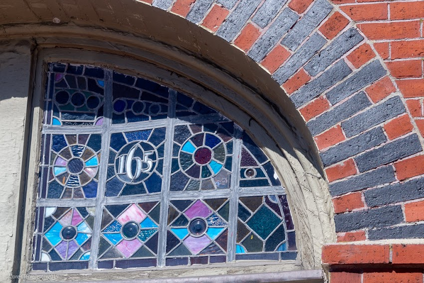 Portland, Maine USA March 2019 photo by Corey Templeton. One of the stained glass windows above 165-167 Congress Street, on Munjoy Hill. This building is known as the Francis W. Cunningham house.