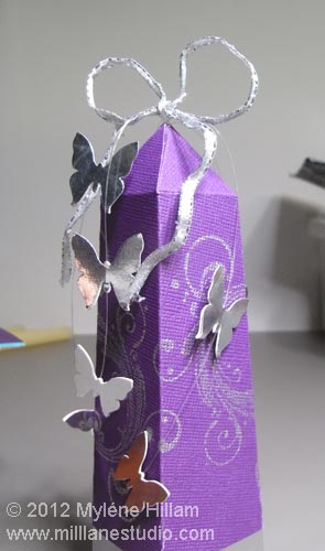 Purple obelisk gift box with mirrored silver butterflies trailing down the box.