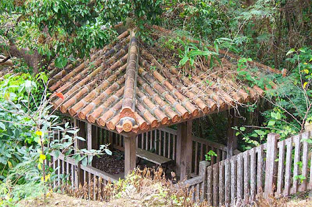 Tiled-roof building overlooking waterfall, benches, fence and railings