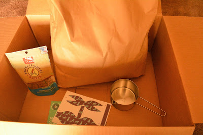 What's inside the box: a plain bag of dog food, a bag of treats, and a couple of cardboard postcards