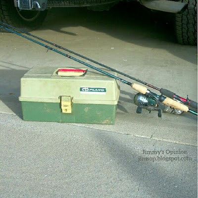 A green plano tackle box with two rod and reels leaning across the top.