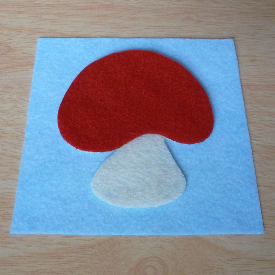 Light blue felt square background with red mushroom applique pieces laid out before sewing