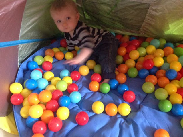 baby in tent with lots of different coloured balls