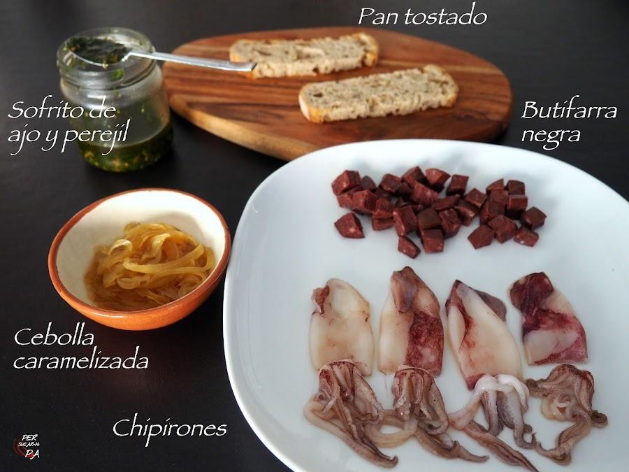 Una tapa gastronómica: base de pan tostado, cebolla caramelizada, dados de butifarra negra salteada y chipirones con su ajo y perejil