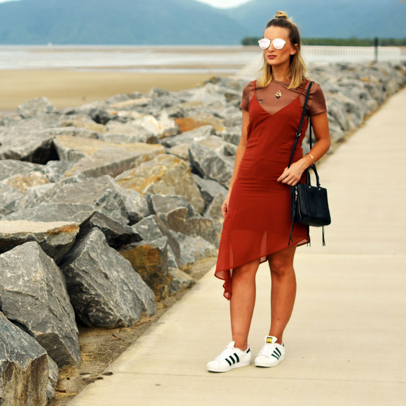 effortlessly stylish layered outfit burnt orange slip dress layered over brown top with adidas sneakers and rebecca minkoff bag