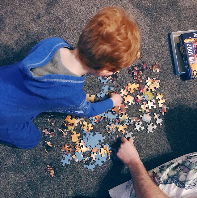 Little boy and his Dad doing a puzzle together on the floor