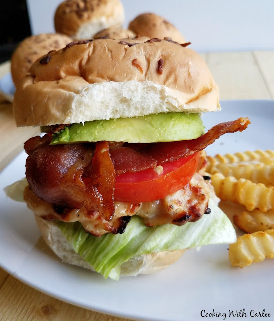 close up of grilled chicken sandwich with tomatoes, bacon and avocado on the sandwich