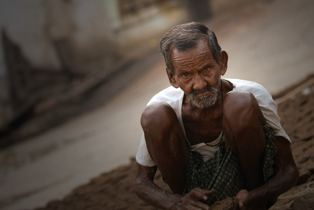 Man in Varanasi, India is making dung of cows, which is used in Hindi religious fire yajna as an important ingredient.