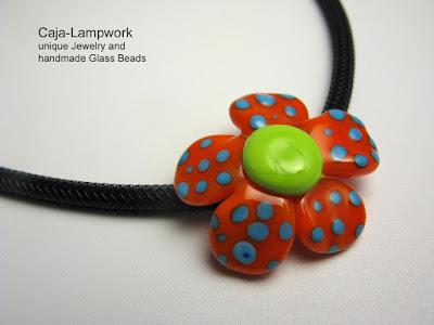 orange-gruene Blume mit tuerkisen Punkten