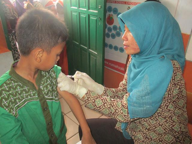 Siswa Kelas 1 SD Juara Cilegon Sedang Disuntik Imunisasi oleh Petugas Puskesmas Kecamatan Cibeber Cilegon