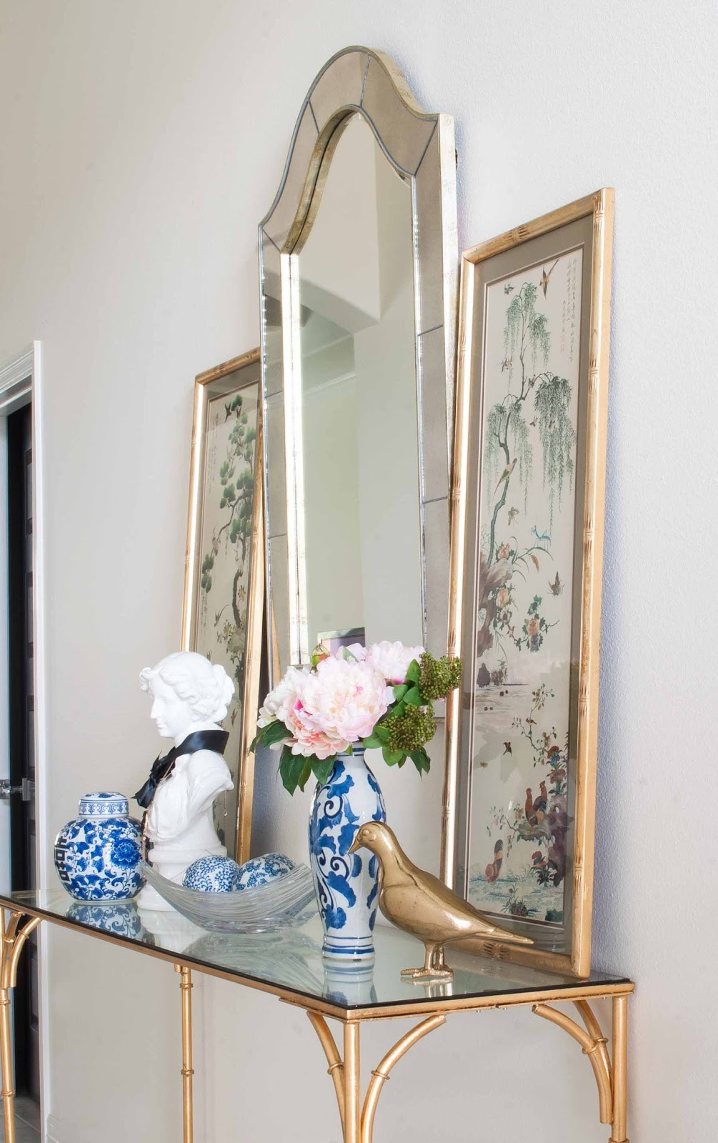 Chinoiserie ginger jars, flowers, vintage art and a gold bamboo console table in a foyer.
