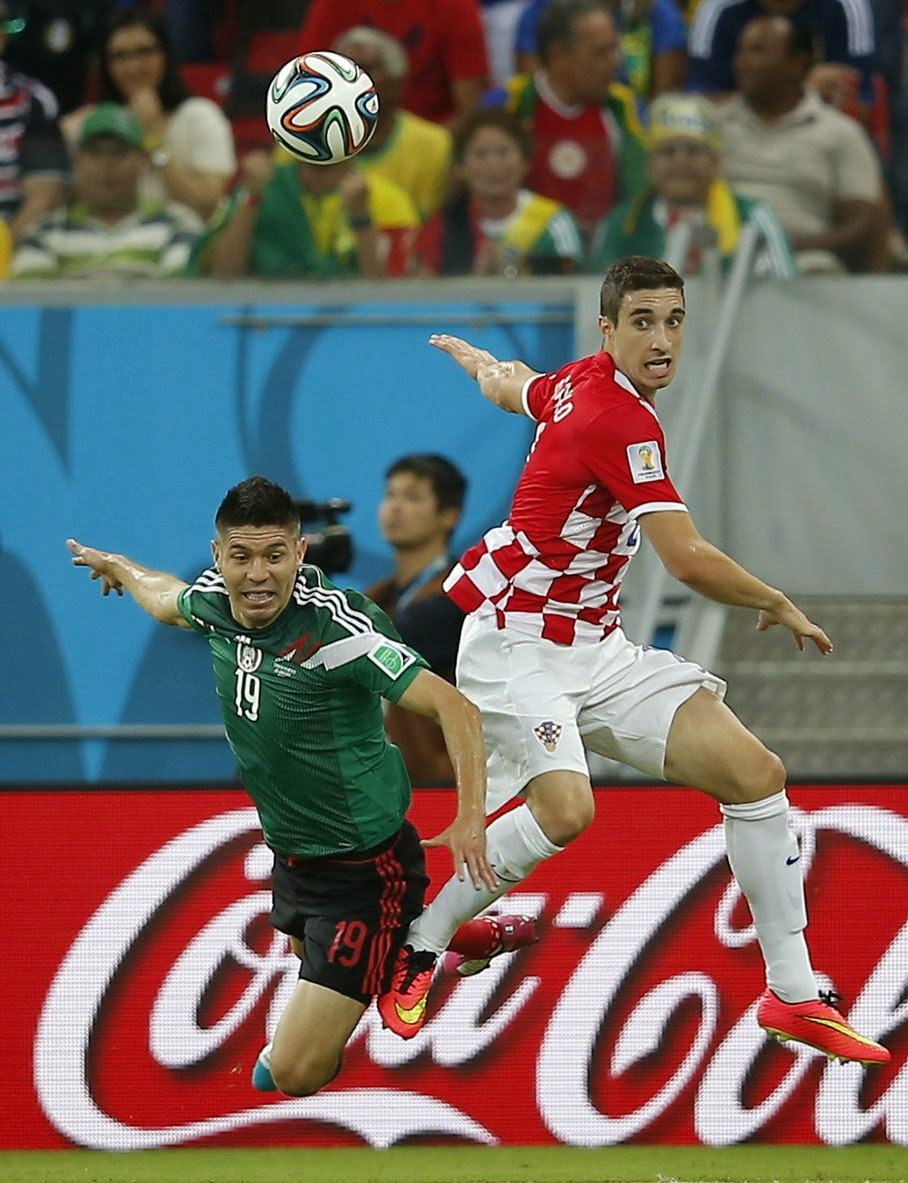 Mexico's Oribe Peralta heads the ball next to Croatia's Sime Vrsaljko during the group A World Cup soccer match between Croatia and Mexico at the Arena Pernambuco in Recife, Brazil, Monday, June 23, 2014.