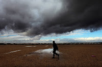 A Syrian refugee walks toward his tent at Zaatari refugee camp through puddles and in front of storm clouds. The new water cycle could push monsoons around the world and cause the Sahara to bloom. (Credit: Mohammad Hannon / AP) Click to Enlarge.